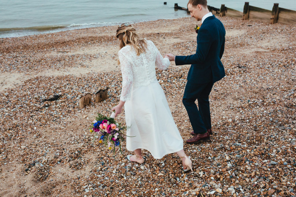A bride and groom walking on the beach in Whitstable at their seaside wedding in Whitstable Kent