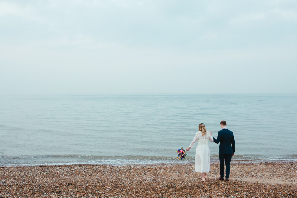 A bride and groom walk to the sea at their seaside wedding in whitstable