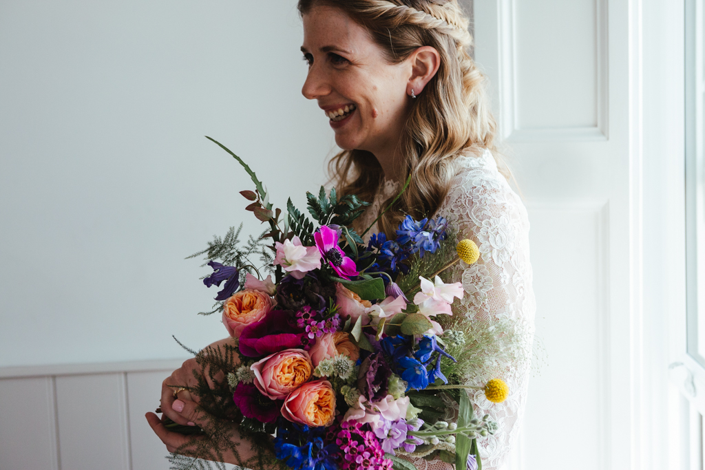 A bride holds a bright flower bouquet by BluBelle Creative
