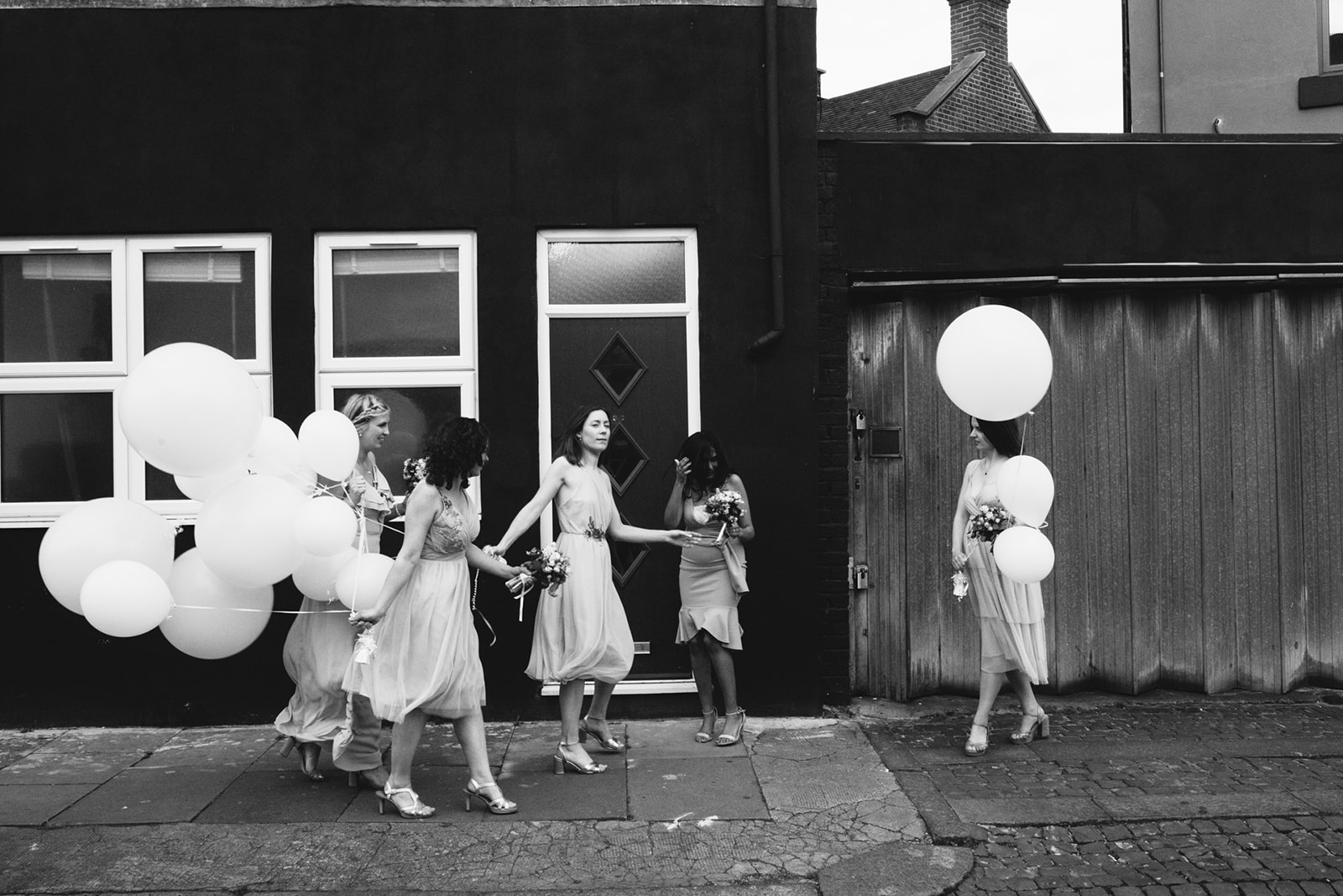 A black and white coloured photo of bridesmaids with large white balloons at a Clapton Social Club Wedding in London