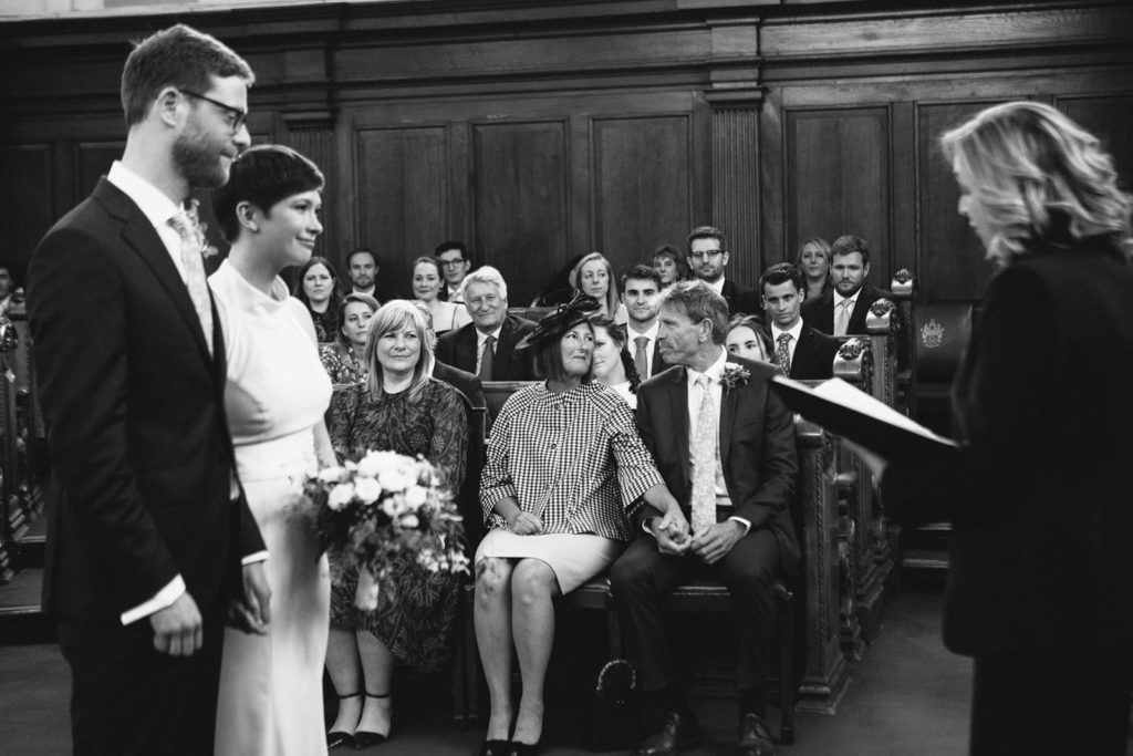 A black and white coloured photo of a wedding ceremony at Islington Town Hall