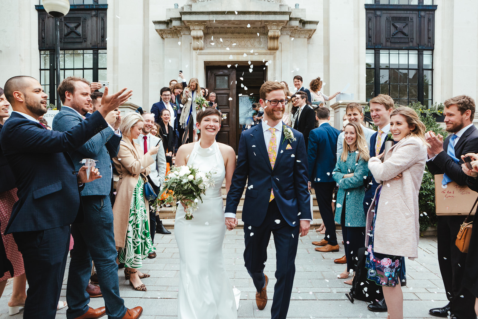 A bride and groom with Confetti on the steops of an Islington Town Hall Wedding