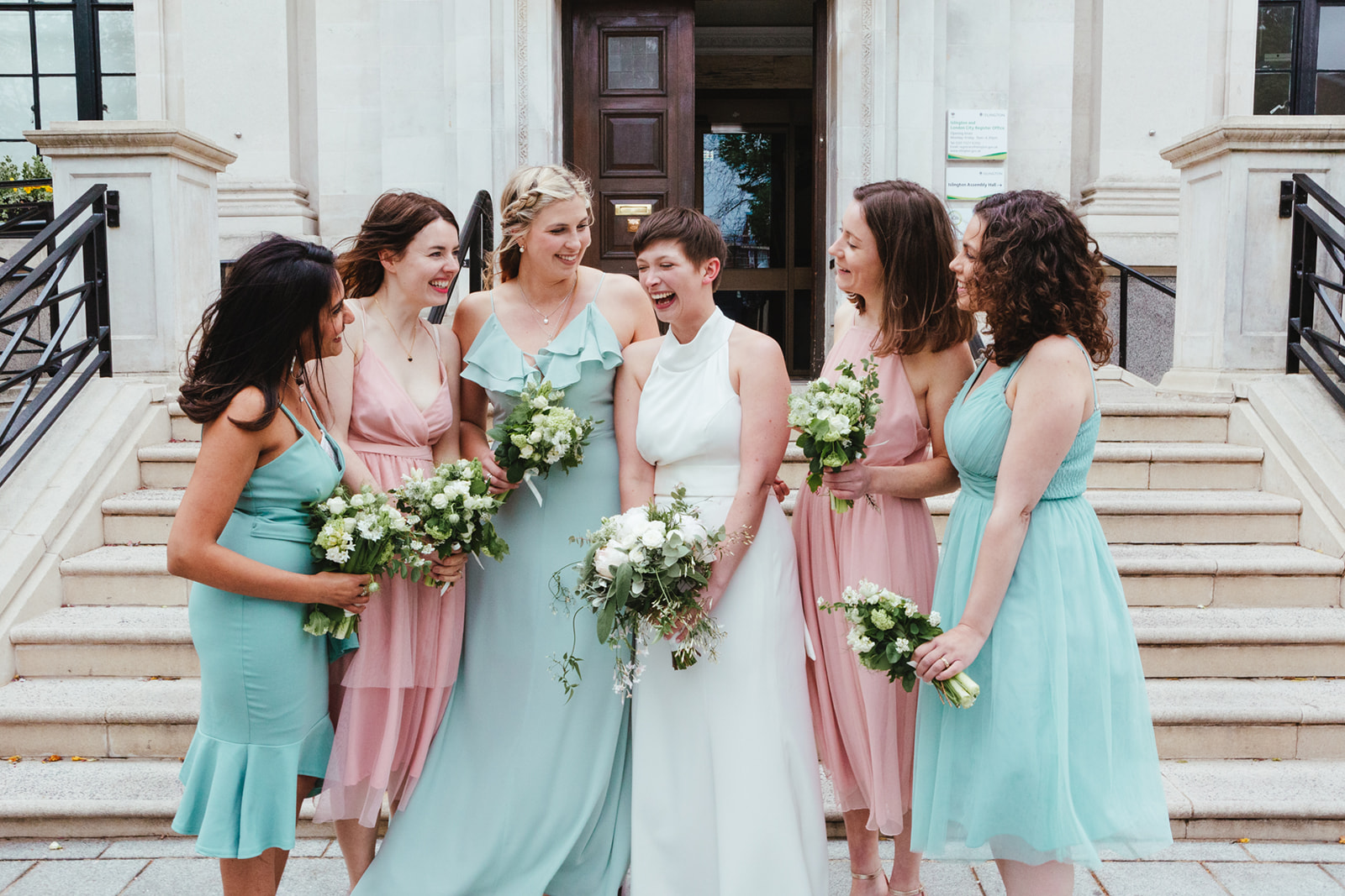 A bride with her bridesmaids standing outside of Islington Town Hall