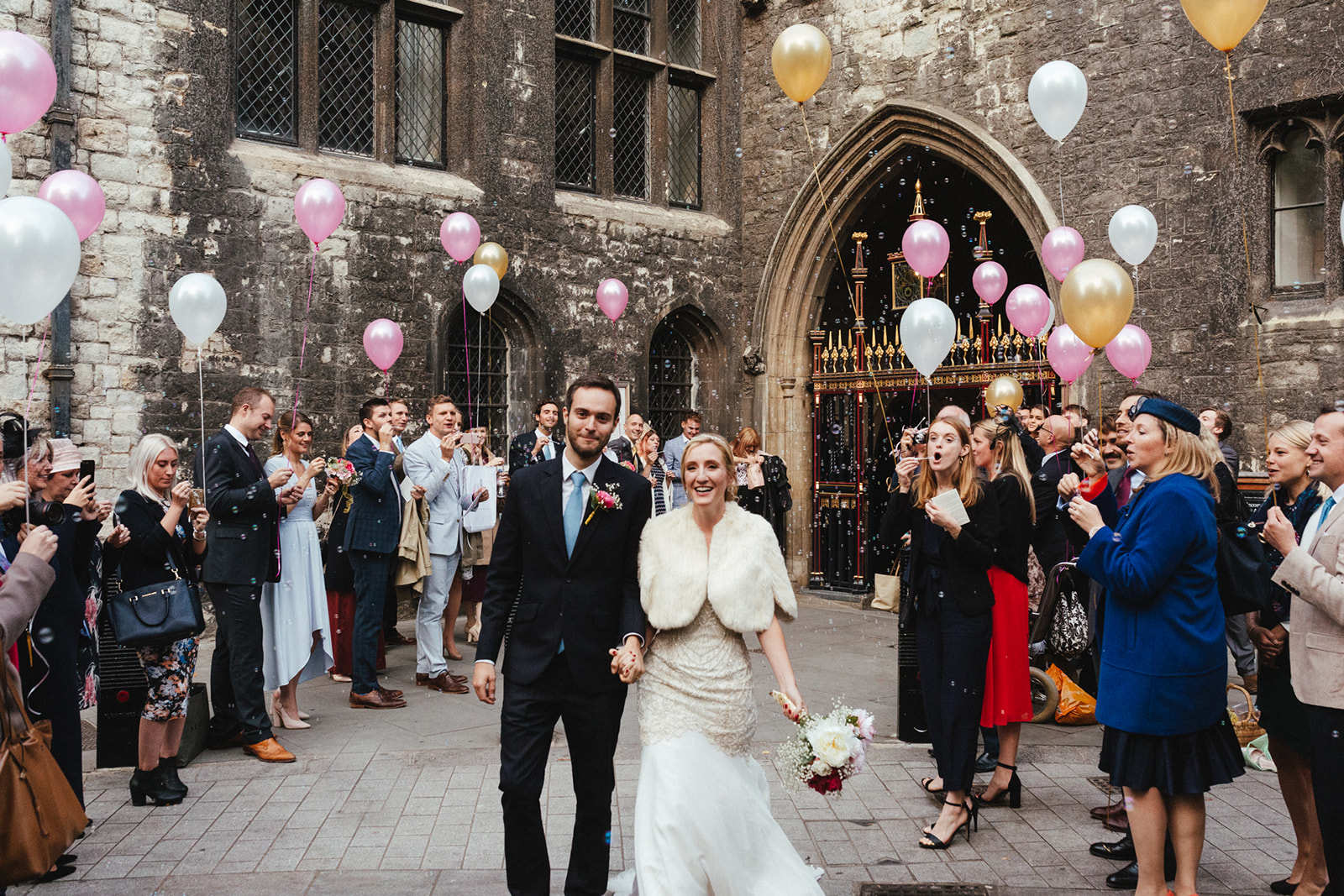 A bride and groom leaves their Westminster Abbey ceremony surrounded by a cloud of balloons
