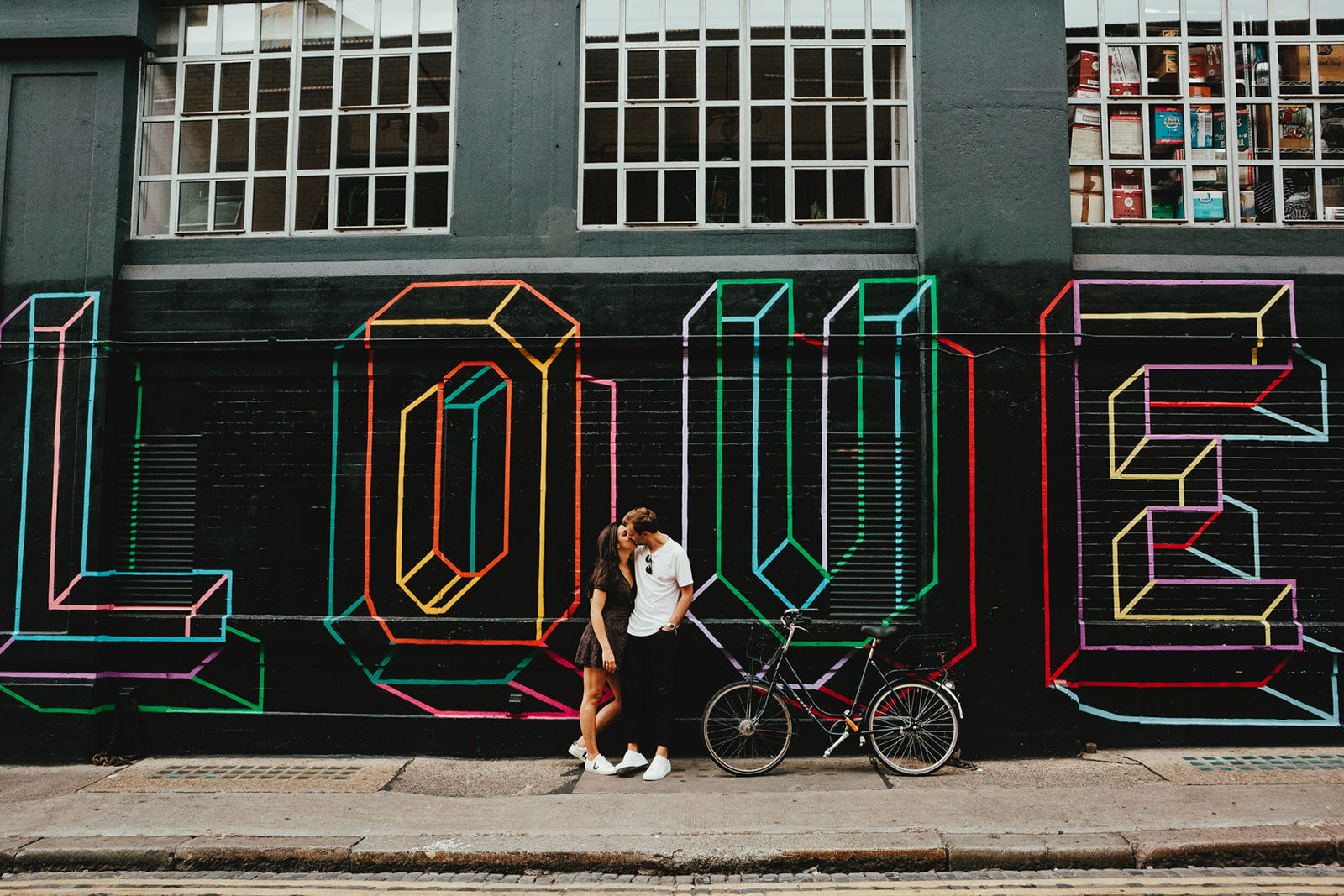 "A young couple pose in front of a graffiti ""Love"" sign on their Shoreditch engagement shoot in East London"