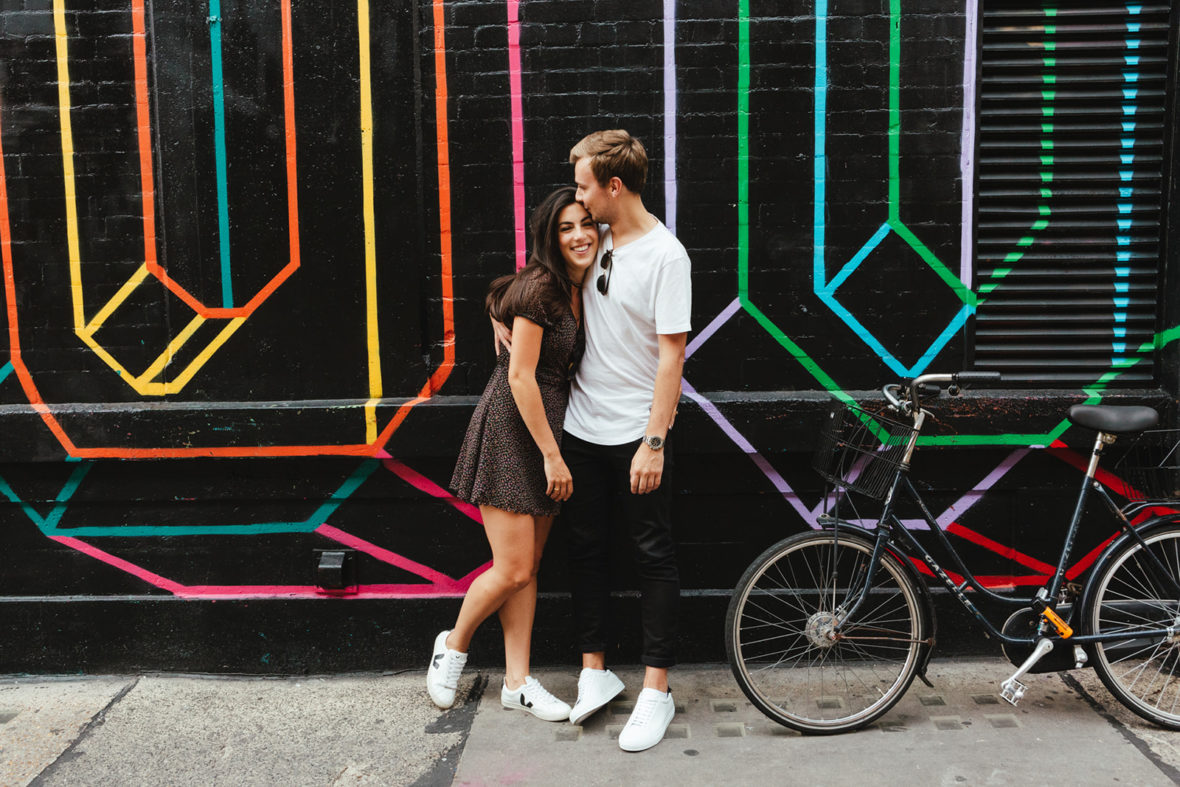 A young couple pose in front of a graffiti
