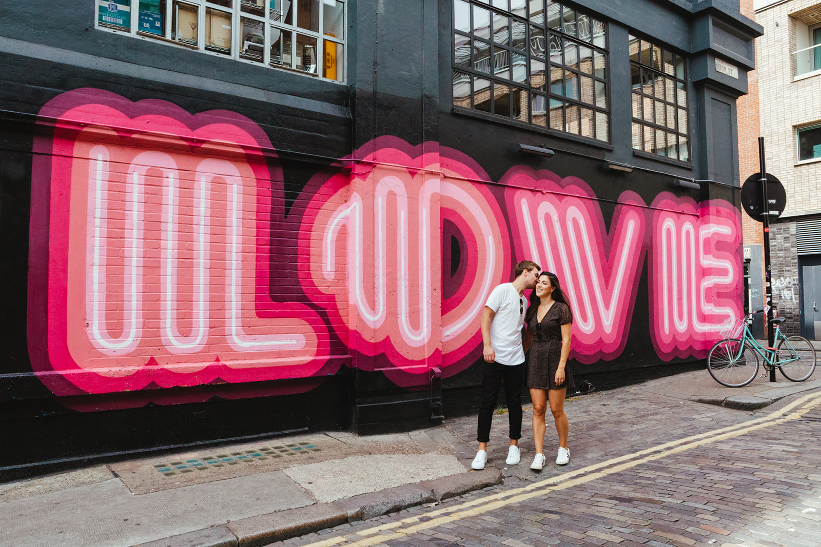"A young couple pose in front of a bright pink graffiti ""Love"" sign on their Shoreditch engagement shoot in East London. Photographed by natural London Wedding photographer Matilda Delves"