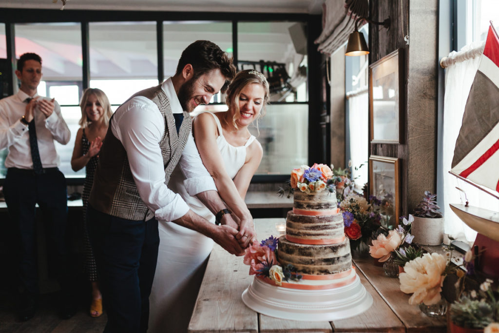 A bride and groom cutting a naked wedding  cake at their The Gallivamt Camber Sands Wedding