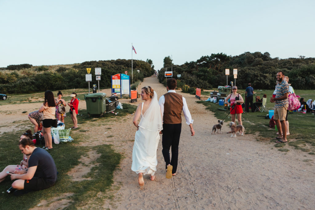 A documentary wedding photograph of a bride and groom on camber sands beach in the summer surrounded by tourists