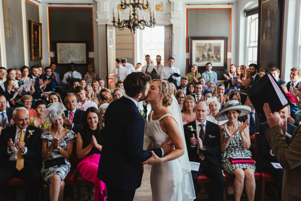 The first kiss of a bride and groom in the Old Town Hall in Rye by Matilda Delves