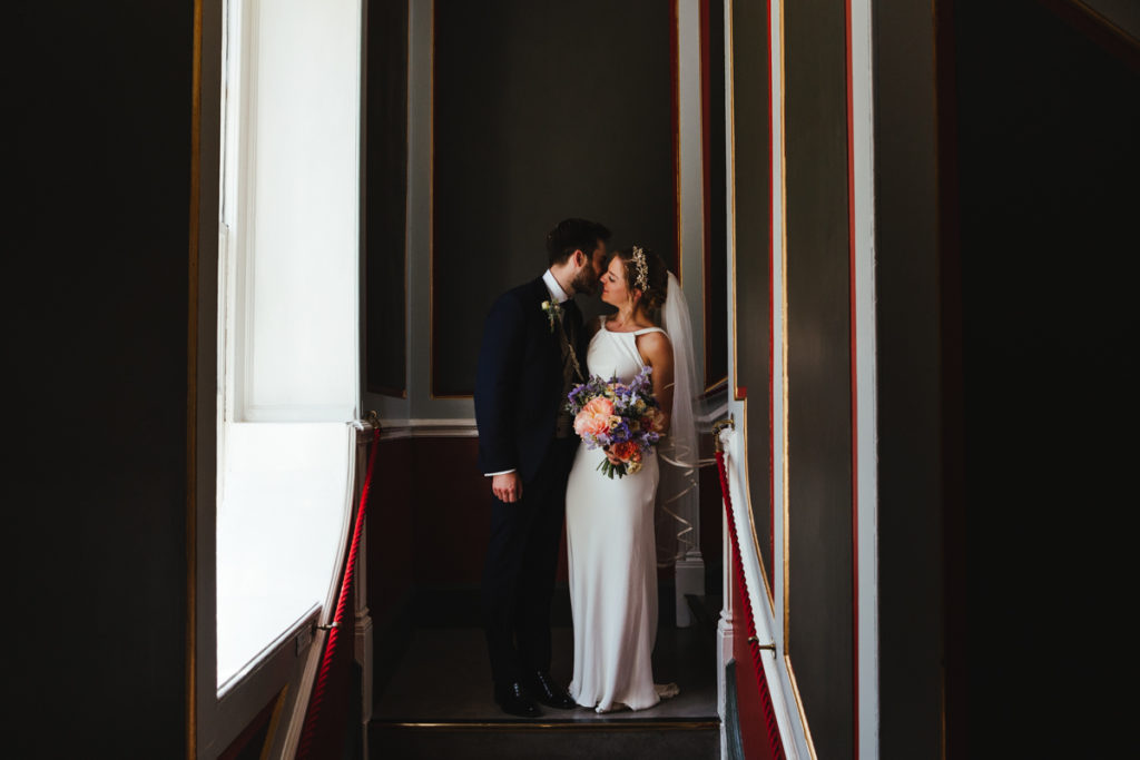 A bride and groom portraits on the stairs of the Town Hall in Rye by Matilda Delves