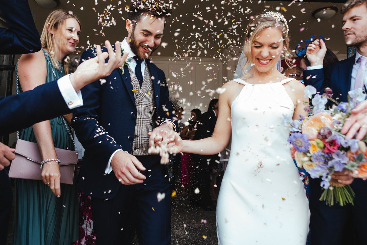 Confetti being thrown over a bride and groom outside of Rye Town Hall photographed by Matilda Delves