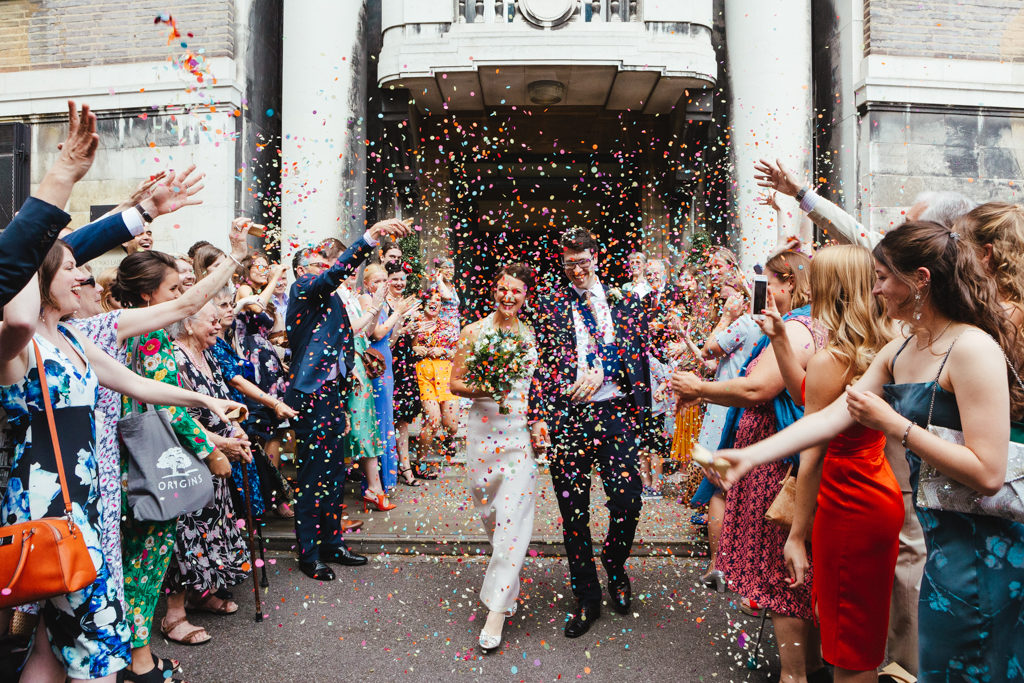 A bride and groom are covered in brightly cloured confetti while leaving their Stoke Newington Town Hall Wedding