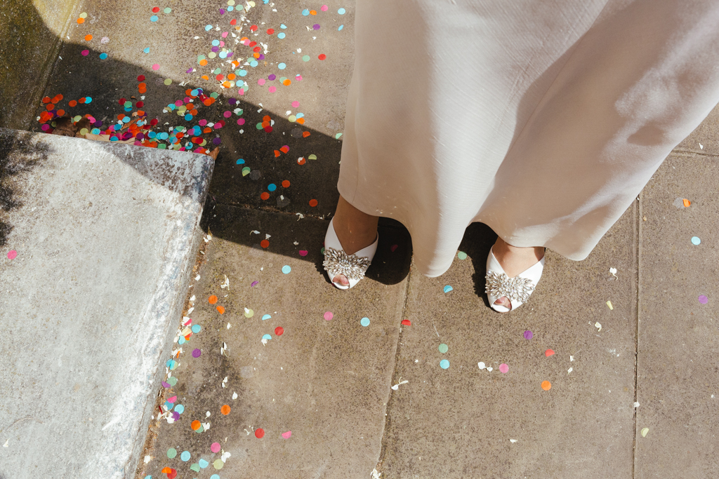 A bride with courful confetti over her feet at a Stoke Newington Town Hall Wedding