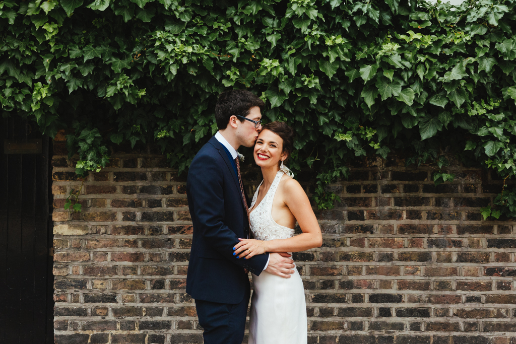 A groom kisses his bride outside of their Islington Town Hall wedding reception