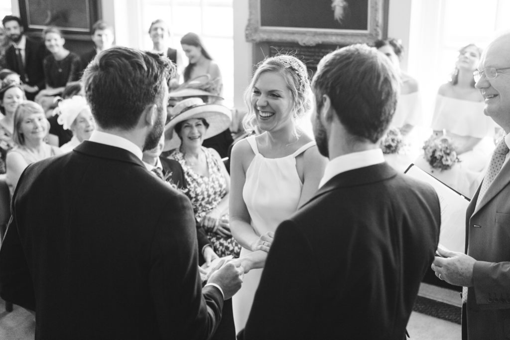 A black and white photograph of a bride and groom saying their vows in Rye Town Hall