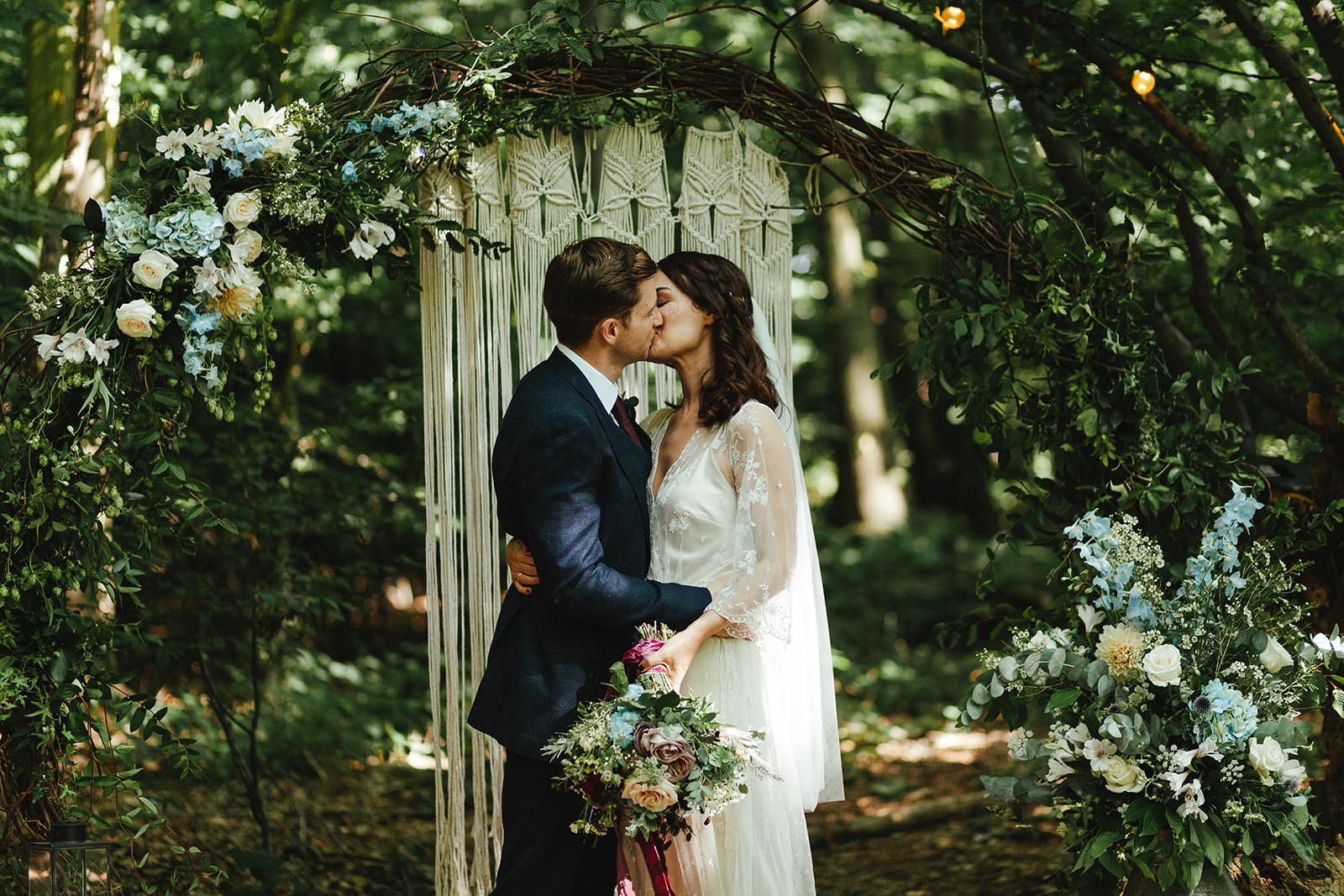 A bride and groom kiss at The Dreys woodland wedding venue
